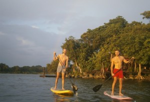 Two guests stand up paddle boarding at Jicaro Island Ecolodge.